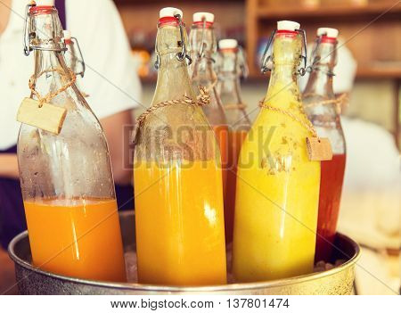 drinks, thirst, refreshment and sale concept - bottles of fruit or vegetable juice in ice bucket at market