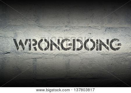 wrongdoing word stencil print on the grunge white brick wall