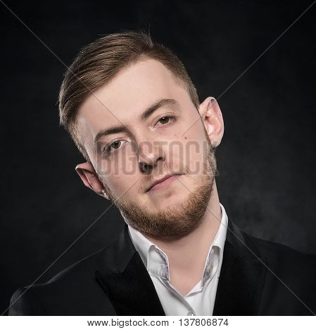 Portrait of a skeptical businessman over dark background.