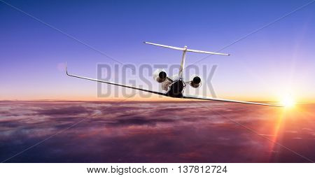 Private jet plane flying above clouds in beautiful sunset. Shot from front view