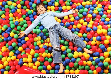 Happy lad seated on colorful balls and looking at camera with smile