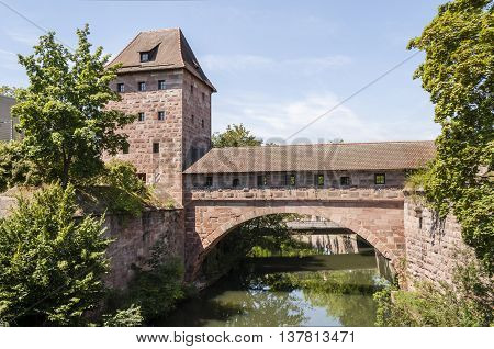 photo depicting an old bridge and tower structure in Nurnberg Bavaria Germany.