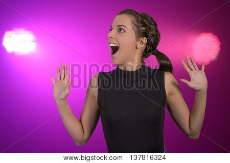 Pretty young lady with excited expression and colorful lights in background