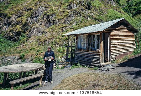 Upper Svanetia Georgia - July 24 2015. Old man stands in front of small bar halfway between Mestia and Ushguli community