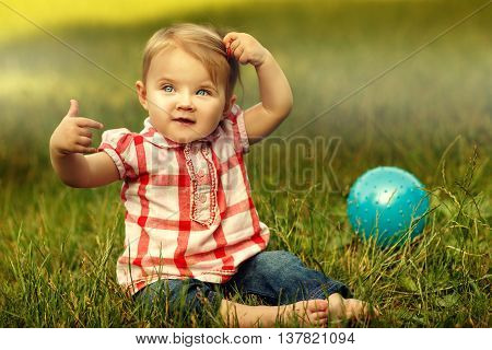 Little cute girl in checked shirt sitting on the grass with blue ball