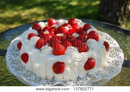 Closeup of a homemade and flower decorated strawberry cake on a table in a garden