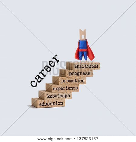 Career ladder growth concept. Superhero on top of the wooden steps. vintage staircase with words: education, knowledge, experience, promotion, progress, success. white background.