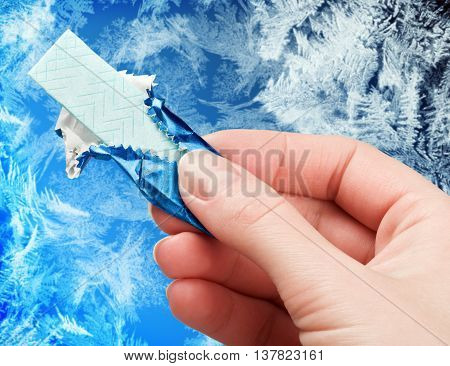 chewing gum in his hand against the frosty background