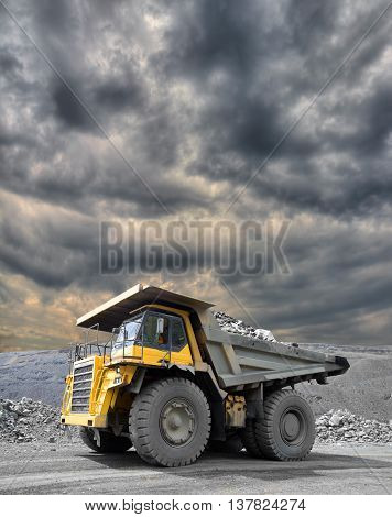 Heavy mining truck driving through the iron ore opencast with dramatic sky on the background
