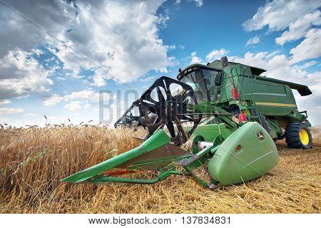 Dobrich Bulgaria - July 08: Modern John Deere combine harvesting grain in the field near the town Dobrich Bulgaria July 08 2016