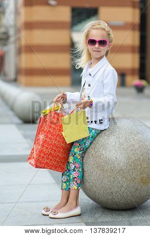 Fashionably dressed little girl with shopping bags. Young little girl with full shopping bags standing near boutique. Portrait of a kid with shopping bags. Blond girl in sunglasses.