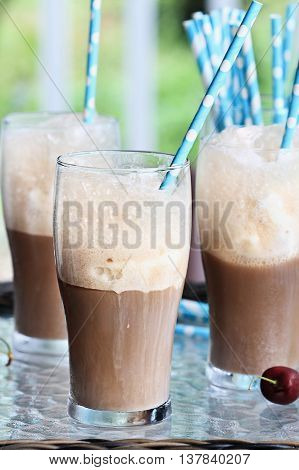 Root beer floats with colorful party straws. Extreme shallow depth of field with focus on center glass.