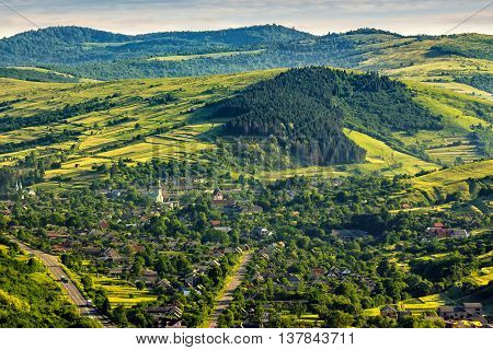 summer landscape. village on the hillside near the forest on mountain at sunrise