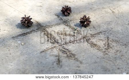 noughts and crosses on the sand, fir cone
