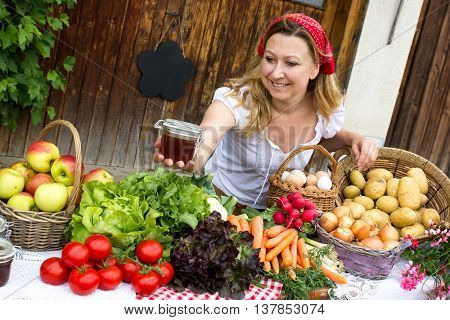 A cute marketwoman offers honey at the market
