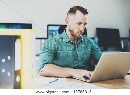 Social Trading Online Public Relations Manger Analyze Reports.Men working wood table Modern Interior Office.Businessman Work Coworking Studio.Using Digital Laptop.Blurred Background.Business Startup
