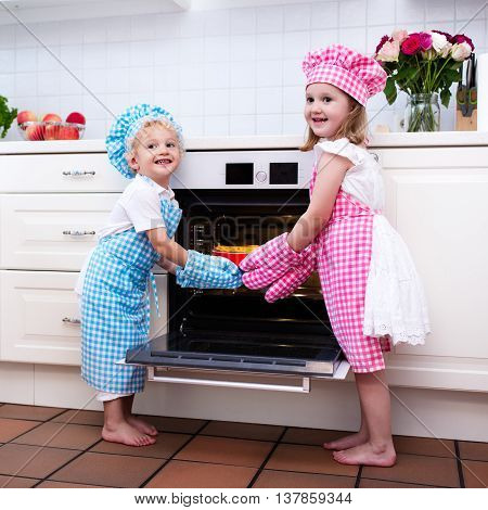 Little boy and girl brother and sister baking delicious apple pie in white kitchen. Kids taking fruit cake out of oven. Children bake at home. Toddler child and preschooler kid cook for the family.