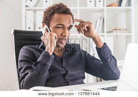 Thinking african american businessman having phone conversation in office. Bookshelf with documents in the background