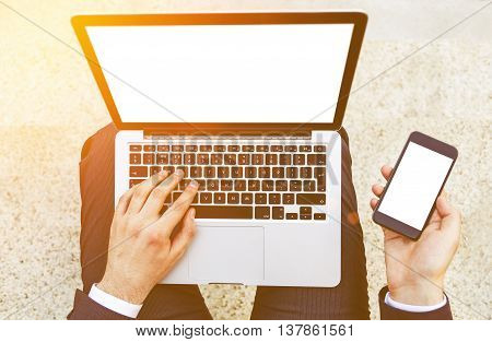 Top view of businessman using laptop and smart phone with blank screens on concrete background. Toned image. Mock up