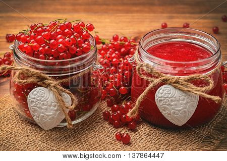 Red currants jam in glass jars on wooden table.