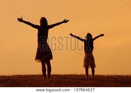 Mother and daughter enjoy in sunset together.