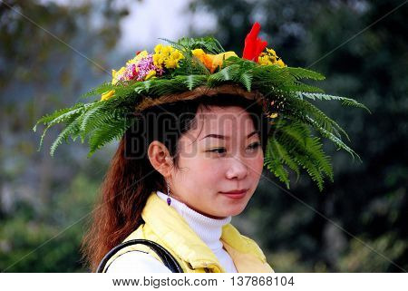 Huang Long Xi China - November 7 2007: Young Chinese women wearing a traditional Huang Long Xi floral wreath hat