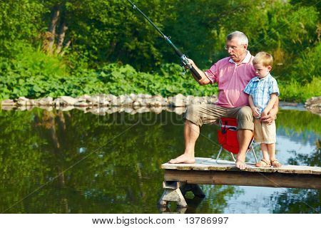 Photo of grandfather and grandson on pontoon fishing on weekend