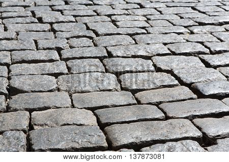 Stone paving texture. Abstract structured background of an old street pavement slabs pattern