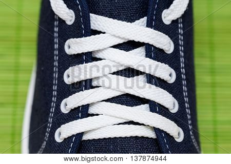 Lacing with white laces at the blue cloth sports Shoe with stitches of white thread. All on a bright green background from bamboo sticks