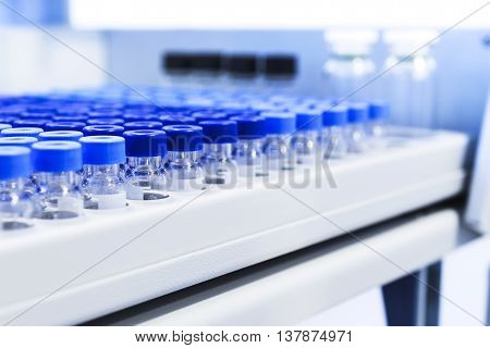 Rows of glass vials in the tray automatic liquid dispenser. Laboratory chemical equipments. Shallow depth of field