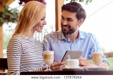 Happy loving couple is dating in cafeteria. They are talking and laughing. Man is sitting at table and holding tablet