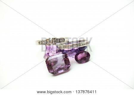 Diamond rings on loose purple amethyst gemstones