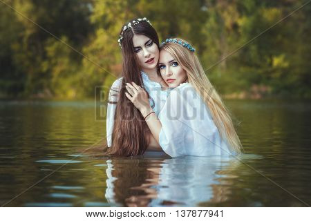 Girls lesbians are embracing they are in the water.