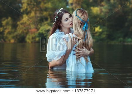 Mistresses women hugging they dressed in white and standing in the water.