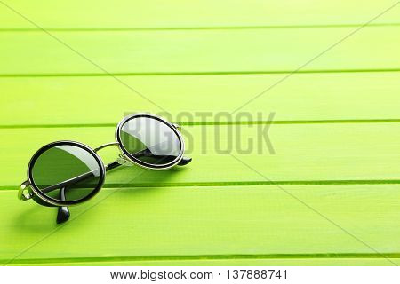 Black Sunglasses On A Green Wooden Table