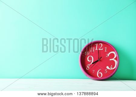 Pink round clock on a green wooden table