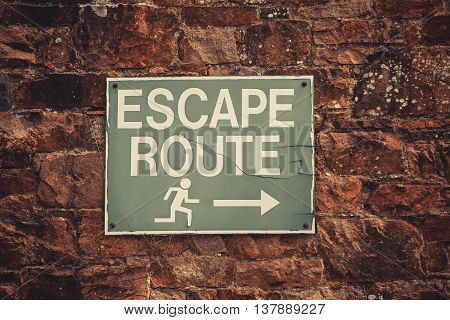 Color image of an Escape Route indicator on a brick wall.
