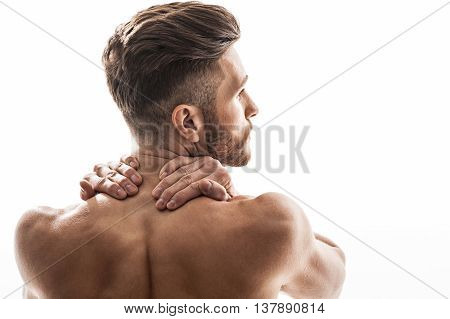 Fit sportsman feels is massaging his neck because of pain. He is standing with naked back. Man is looking aside pensively. Isolated and copy space in right side