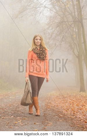 Fashionable woman posing in foggy autumn park. Pretty young girl in sweater pullover with handbag in forest. Fall fashion vogue.