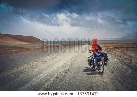 Solo female cyclist on the bicycle in the stunning remote part of Western Tibet