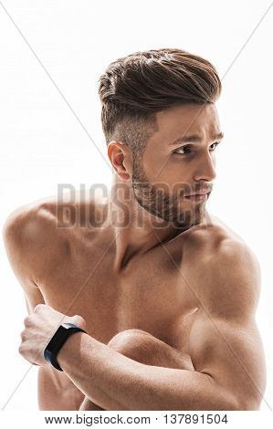 Fit young man is having rest after exercising. He is sitting while leaning arm on leg. Sportsman is looking aside with seriousness. Isolated