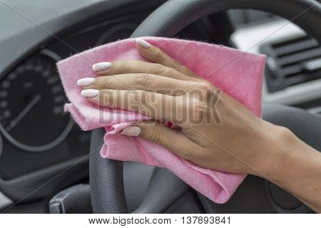 Girls pink cloth wipe the hand wheel in the car.