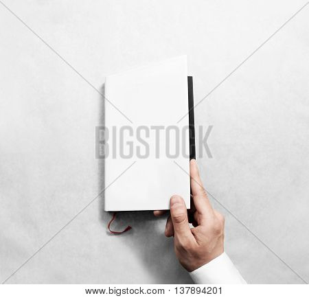 Hand opening blank white book cover mockup template. Clear booklet front surface design mock up. Arm holding opened textbook diary. Reading clean notebook copy. Closed catalogue presentation display.