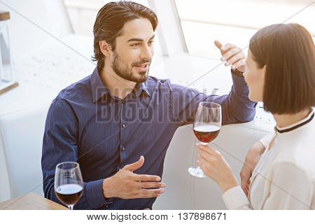 Cheerful loving couple is dating in restaurant. Man is talking with aspiration and smiling. Woman is listening to him attentively. They are sitting and drinking wine