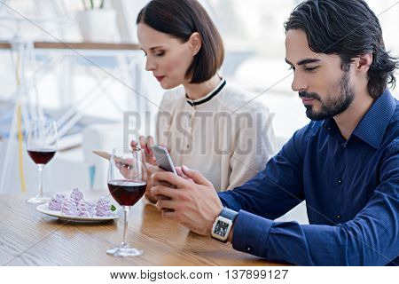 Modern technology instead of communication. Man and woman are using smarphones with joy. They are sitting at table near food and glasses of wine