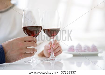 Cheers. Loving couple clinking glasses with red wine. Focus on their hands