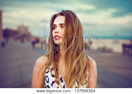 Beautiful young girl walking on city ocean beach boardwalk at sunset time and wind blowing up her hair. Woman looking to the side outdoors.