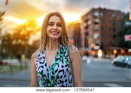 Beautiful young blonde woman walking on city street at sunset time. Woman is happy and smiling wearing casual summer dress.