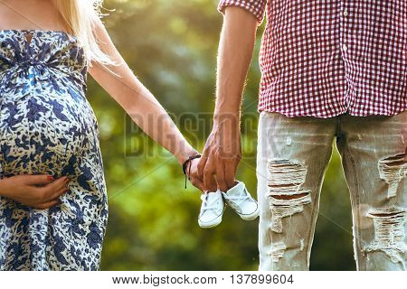 Family together holding baby shoes in hands and standing the summer park. Woman is pregnant. Happy couple waiting for a baby.
