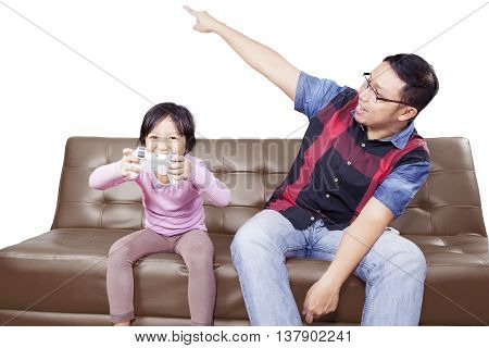 Little girl playing video game while father scolding at her isolated on white background